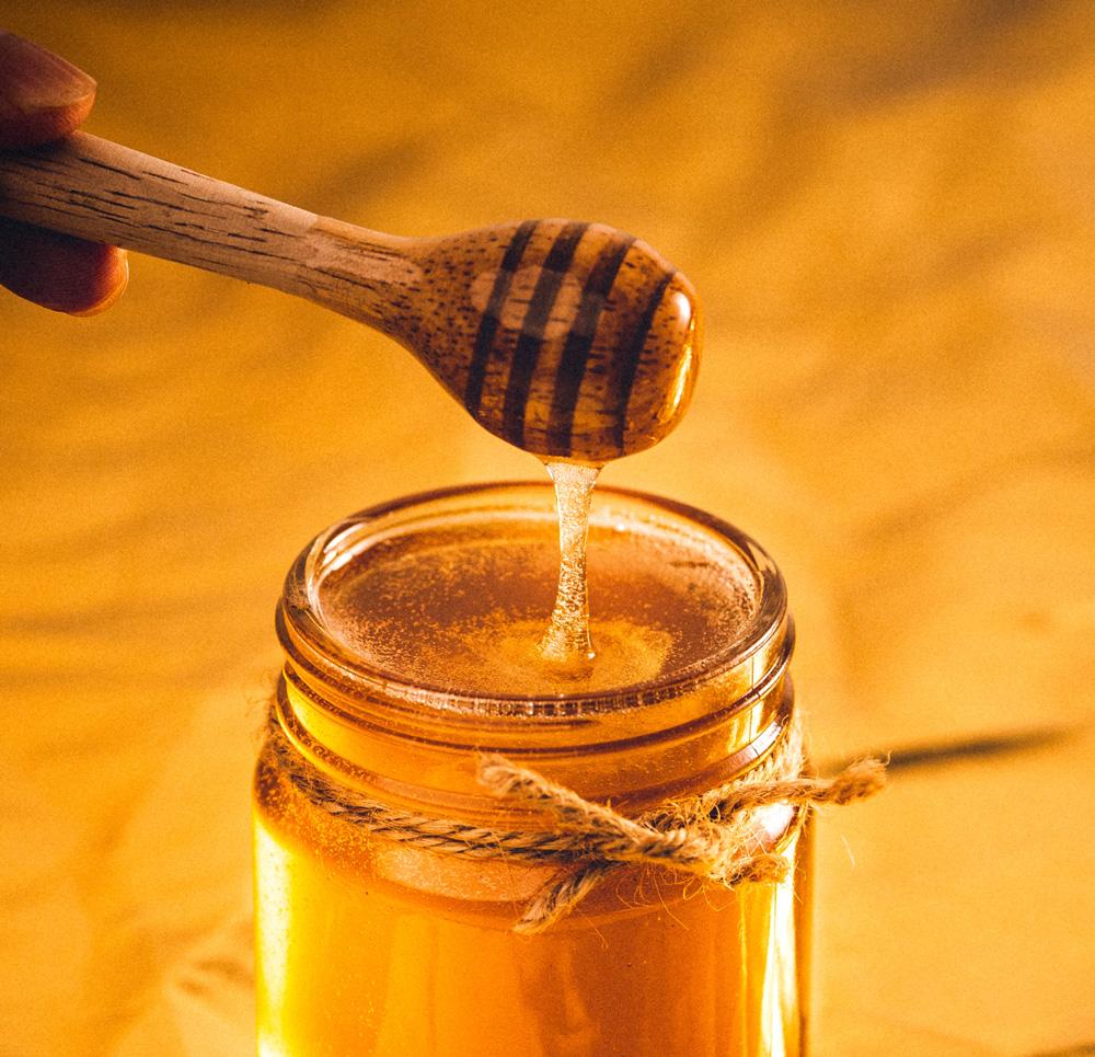 Wood honey spoon in a honey jar.